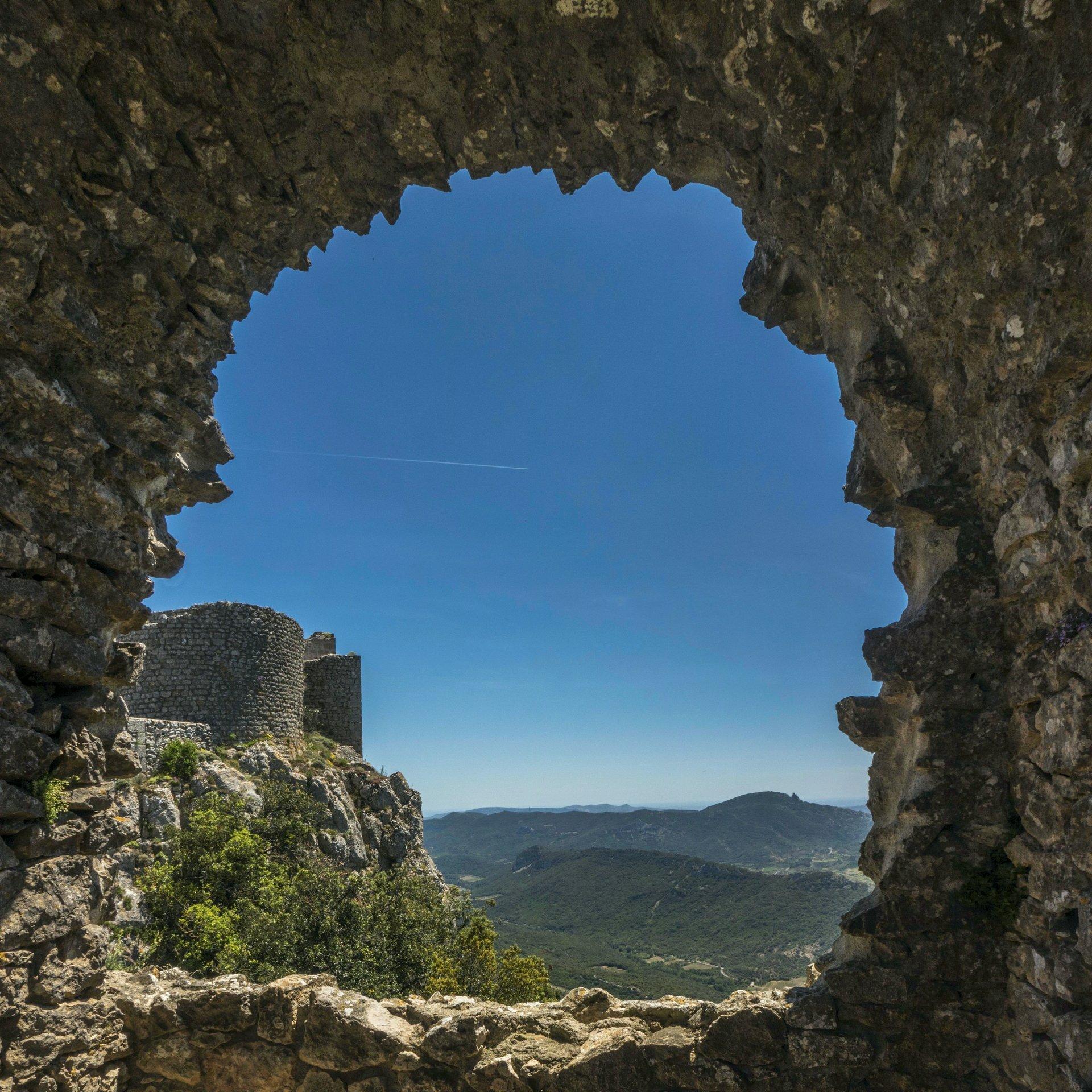 Fensterblick von der mittleren Ringmauer auf den Donjon der unteren Burg von Château de Peyrepertuse und auf Château de Quéribus